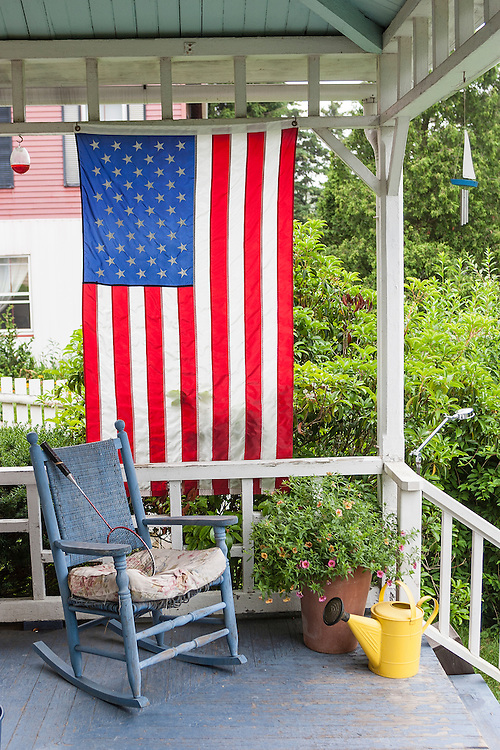 American flag hangs from old fashion porch with rocking chair, watering can and badminton racquet