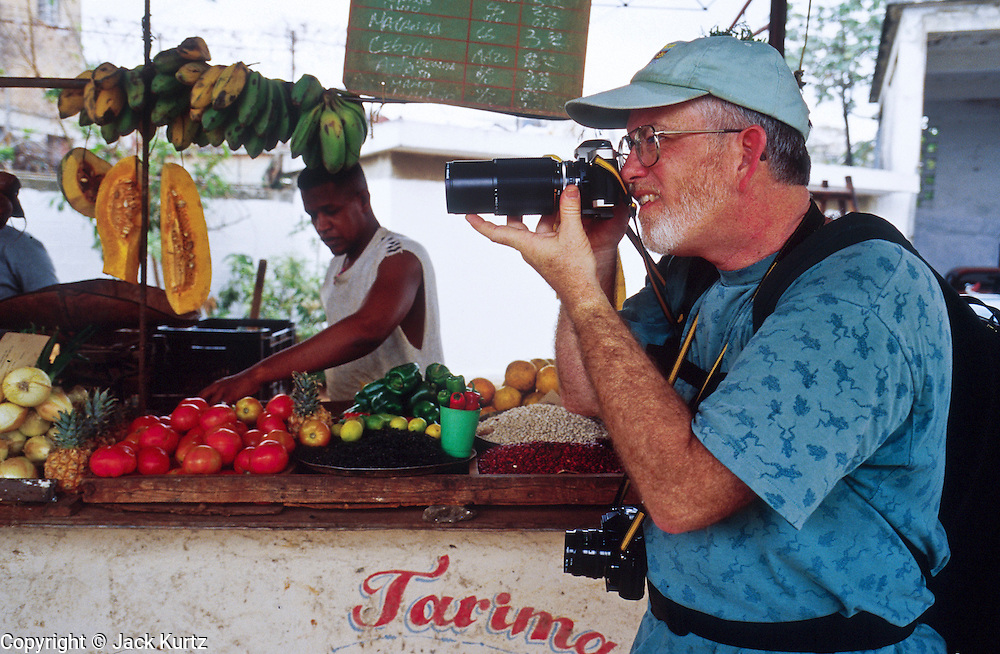 MARCH 19, 2001 - HAVANA, CUBA:  An American tourist photographs in the farmers' market in the Regla neighborhood  of  Havana, Cuba, March 19, 2001.  Tourism in Cuba is expanding rapidly and has become a key source of foreign exchange for the Cuban government. Hundreds of thousands of Americans travel illicitly to Cuba because the US government, through the US economic embargo against Cuba, restricts the way and how much money Americans can spend in Cuba.      PHOTO BY  JACK KURTZ     ECONOMY  POVERTY  TOURISM  FOOD