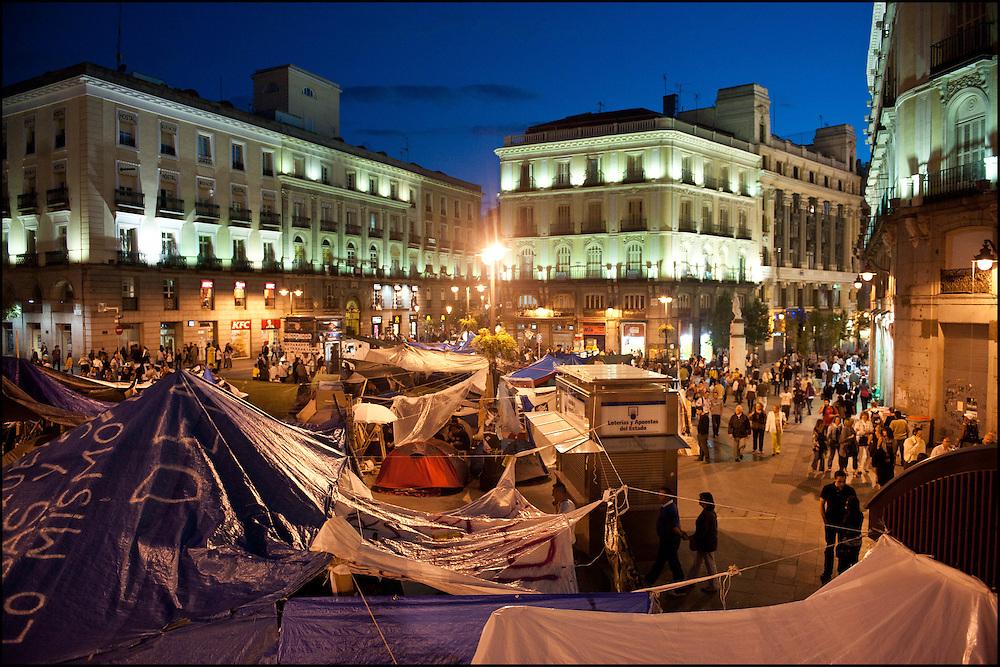 """Vue de la partie Sud du campement a la tombee de la nuit. // Le mouvement spontane du """"15 M"""" (15 mai) compose de citoyens espagnols campe depuis 2 semaines sur la place Puerta Del Sol avec pour revendication la construction d'une democratie nouvelle. Organise en commission les citoyens prennent la parole lors d'assemblee ouverte a tous - Place Puerta Del Sol à Madrid le Juin 2011. ©Benjamin Girette/IP3Press"""