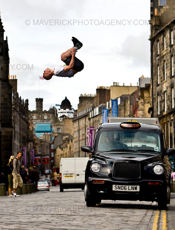 "..Stefan Brown leaps over a taxi on Edinburg's Royal Mile to launch the new ""Urbathon"" event to be held in Scotlands capital...HUNDREDS of runners will have the chance to jump, climb and crawl their way through the capital in the first  10 kilometre race of its kind to take place in Scotland which involves obstacle course challenges. ..Picture Michael Hughes/Maverick"