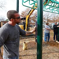 Thomas Wells | BUY AT PHOTOS.DJOURNAL.COM<br /> Trey Permenter of Tidwell Construction makes sure his pole is square before securing it in place and moving on to the next one as he helps install new playground equipment at Milan Elementary School on Wednesday.