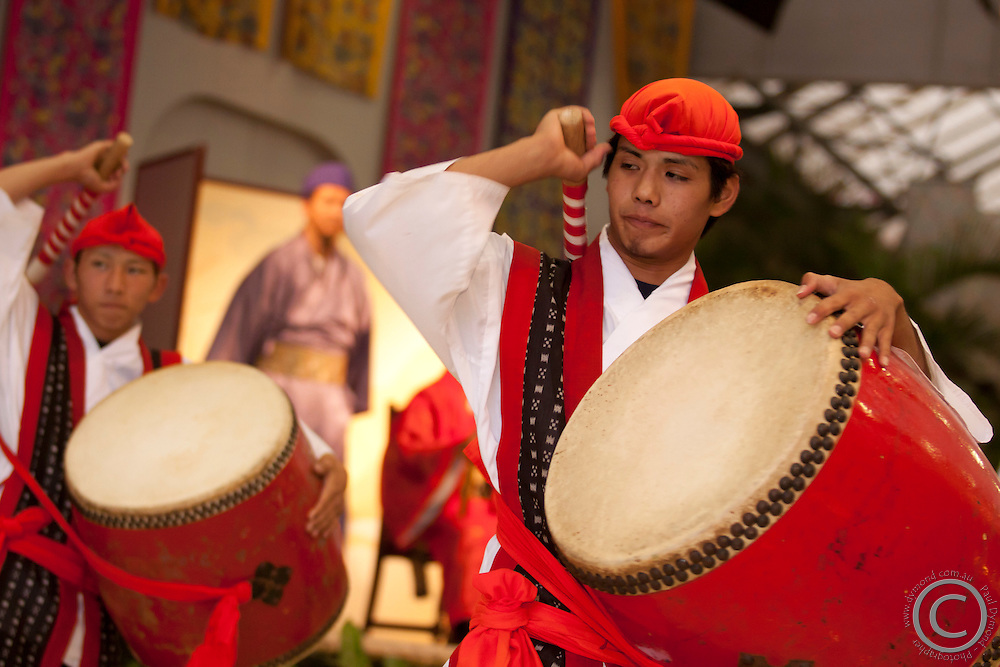 Young men perform the traditional Okinawan drum for tourists visiting the Rykyu Mura on the main island of Okinawa, Japan.