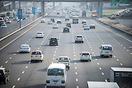 Road traffic in Dubai on Sheikh Zayed Road with cars travelling away from camera. Six lane carriageway of a twelve lane motorway. Highway with many lanes and cars taking commuters to work in busy city urban environment.