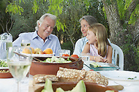 Grandparents with granddaughter (5-6) sitting at garden table