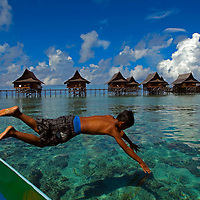 A boy dive from a boat at Sipadan-Kapalai Dive Resort off the coast of Semporna on the state of Sabah on Borneo Island. The island of Kapalai was a beautiful island 200 years ago, but now it is only a sand bar. Erosion has reduced the island to sea level.