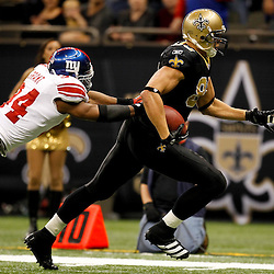 November 28, 2011; New Orleans, LA, USA; New Orleans Saints tight end Jimmy Graham (80) runs past New York Giants safety Deon Grant (34) for a touchdown during the third quarter of a game at the Mercedes-Benz Superdome. Mandatory Credit: Derick E. Hingle-US PRESSWIRE