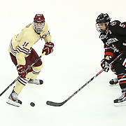 Adam Gilmour #14 of the Boston College Eagles and Matt Benning #5 of the Northeastern Huskies fight for the puck during The Beanpot Championship Game at TD Garden on February 10, 2014 in Boston, Massachusetts. (Photo by Elan Kawesch)