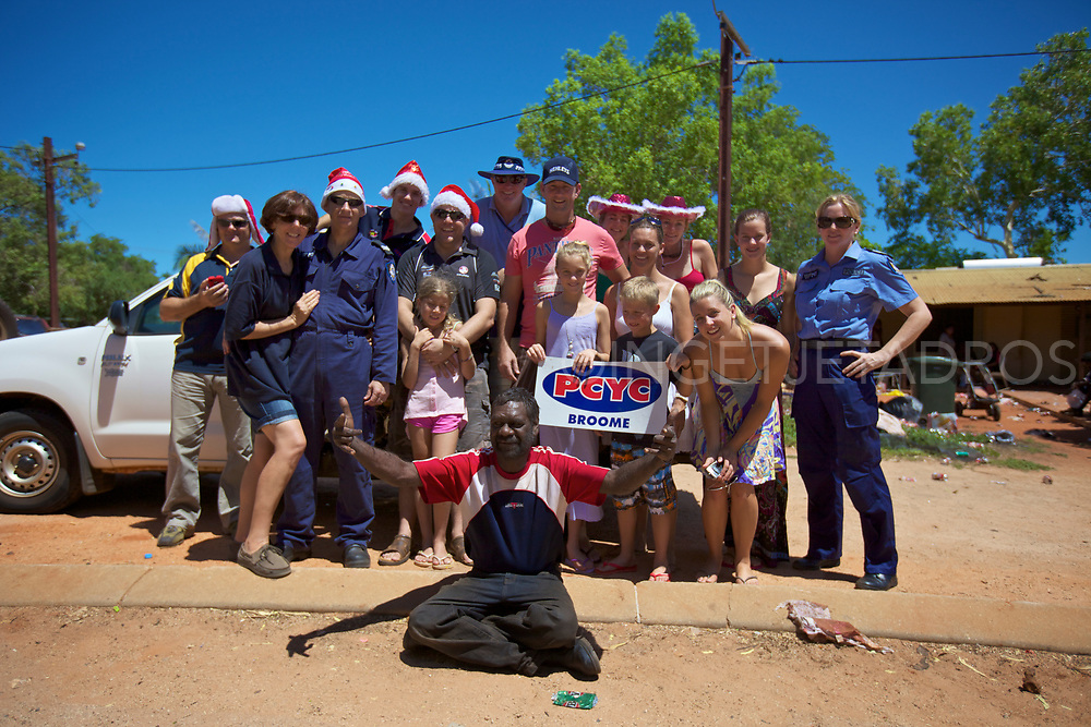 Volenteers and police posing with a member of the One Mile community after a present drop. The Broome Police & Community Youth Centres (PCYC) organise  a present drop each year to bring festive spirit to unprivileged children of Broome. One Mile community, WA