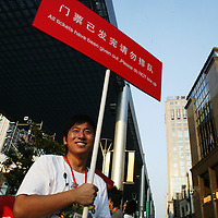 BEIJING, AUGUST 5 :  a volunteer stands in one of the places where Beijingers can watch live broadcasts of the Olympic Games.