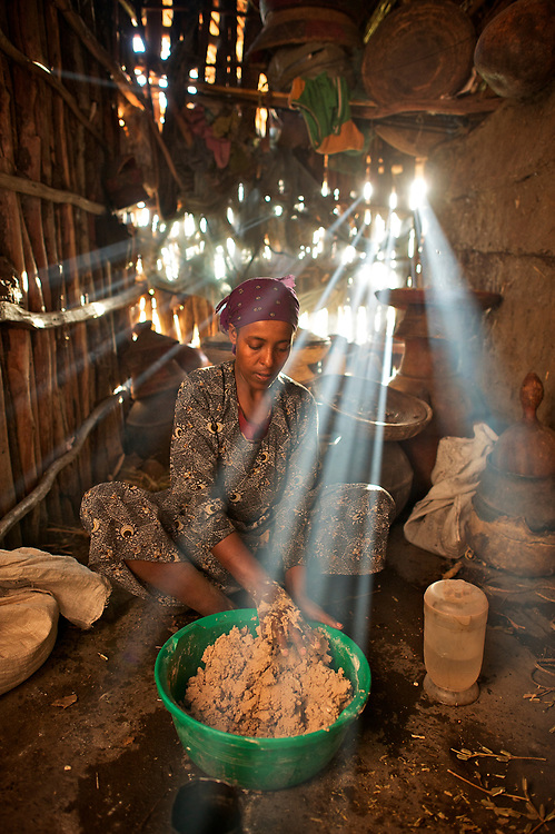 Tayitis Mohammed mixes injera out of teff flower and water in her house in Fontanina near Kombulcha in the Wollo region of the Ethiopian highlands. Injera is the staple bread of Ethiopia, which makes teff a valuable grain. Smoke from the kitchen fire made the rays of the setting sun show up brightly in the dark cookng area to the side of the main room of the stick and clay built house. The walls of the house are caulked with teff straw as well.