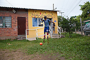 A young boy playing football whilst wearing stilts outside the community library, Biblioteca Comunitaria do Arquipelago, Porte Alegre, Brazil. <br /> <br /> Once a week the children have a music and poetry session where they go out in to the community on stilts singing, playing music and reciting poetry.<br /> <br /> Cirandar is working in partnership with  C&A and C&A Instituto to implement a network of Community Libraries in eight communities of Porto Alegre.