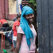 Quasi 800 profughi di cui più di 100 bambini vengono ospitati nella struttura di accoglienza Baobab di Via Cupa a Roma. La struttura può accogliere circa 220 migranti. Semplici cittadini e il gruppo SEL hanno raccolto generi alimentari da distribuire agli all'interno della struttura. Una givane donna mentre esce dal centro sorride.