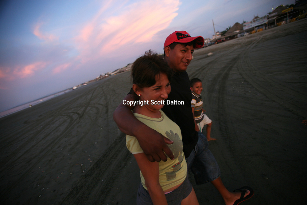A family walks on the beach in Manta, Ecuador on April 14, 2008. Currently the United States uses an air base in Manta to conduct drug-trafficking surveillance flights. The United States military presence helps to contribute an estimated $6.5 million annually to the local economy, but the Ecuadorian government is looking into the possibility of closing the US base once the lease runs out in 2009. (Photo/Scott Dalton).