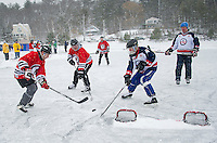 John Mercer and Dave Dolan of The Ice Sages team battle for the puck with Peter Tufts from Essex 73's team during day one of the New England Pond Hockey Classic on Lake Waukewan on Friday.  (Karen Bobotas/for the Laconia Daily Sun)