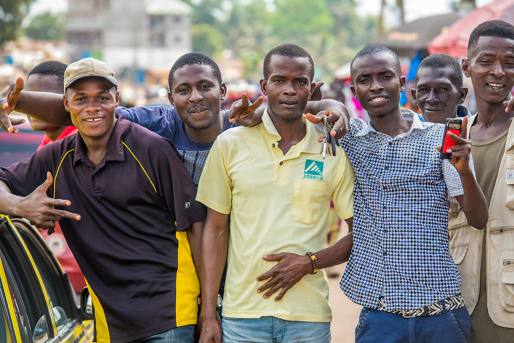 A group of men, smiling, pose for the camera in  Ganta Liberia