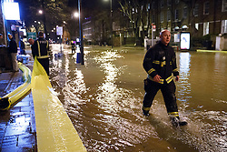 © licensed to London News Pictures. London, UK 27/02/2014. Firemen trying secure the area after a burst main has flooded Clapham Road in south London on Thursday, 27 February 2014. Photo credit: Tolga Akmen/LNP