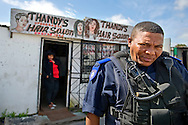 A member of the Anti-Land Invasion Unit walks away after questioning a woman working next to an illegal dwelling in the township of Gugulethu on September 25, 2013 in Cape Town, South Africa. The controversial unit is a division of the Cape Town law enforcement that hires and provides protection for a contract demolition company as they tear down illegal shacks sitting on land owned by the city and designated for residents on the housing wait list. Ann Hermes/© The Christian Science Monitor 2013