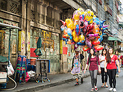 "07 FEBRUARY 2016 - BANGKOK, THAILAND: A man selling inflatable toys for Chinese New Year walks down a street in Bangkok's Chinatown neighborhood. Chinese New Year, also called Lunar New Year or Tet (in Vietnamese communities) starts Monday February 8. The coming year will be the ""Year of the Monkey."" Thailand has the largest overseas Chinese population in the world; about 14 percent of Thais are of Chinese ancestry and some Chinese holidays, especially Chinese New Year, are widely celebrated in Thailand.        PHOTO BY JACK KURTZ"