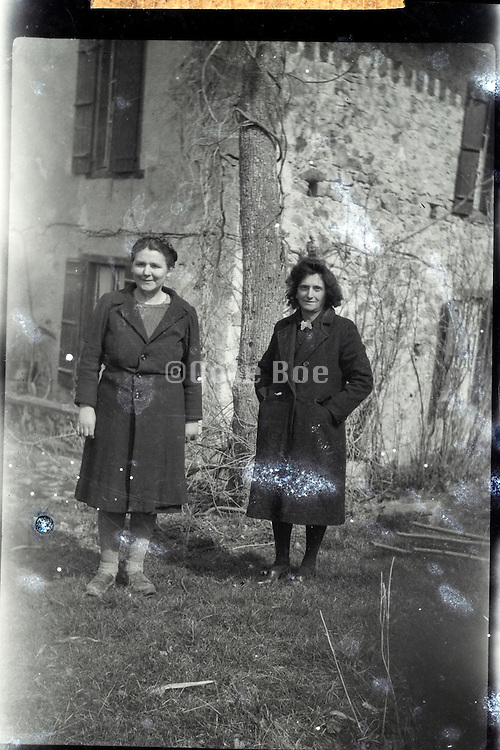 fading photograph of two woman standing in front of a house countryside 1950s Europe