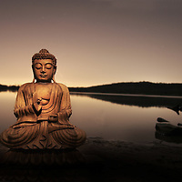 Buddha by a calm lake with reflections