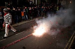 """© London News Pictures. 05/11/2013 . Lewes, UK. A firework exploding as Bonfire societies parade through the streets of Lewes, East Sussex, during as part of traditional bonfire night celebrations. Thousands of people line the narrow streets as bonfire societies parade in costume with the evening ending in the burning of the """"guy"""". Bonfire Night marks the date of the uncovering of the Gunpowder Plot in 1605 and commemorates the memory of the seventeen Protestant martyrs. Photo credit : Ben Cawthra/LNP"""