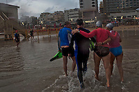 People who go to swim every morning at sunrise at the beach of Tel Aviv
