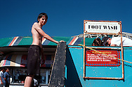 Young man standing next to the foot wash sign, Santa Cruz Boardwalk, California