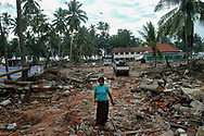 A woman salvaging building materials at the place where the December 26, 2004 tsunami derailed a passenger train killing hundreds of people and destroying the village. Seenigama, Sri Lanka. 19/01/2005. Photo © J.B. Russell
