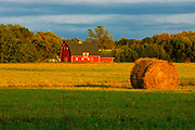 Red barn and bale at sunrise<br />