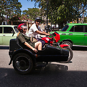 Cubans manage their daily life in the colonial city of Matanzas walking or riding bicycles to most places and doubling up on old classic cars and motorcycles. A couple riding a Jawa 350, a motorcycle, produced by Jawa Moto in Czechoslovakia. <br /> Photography by Jose More