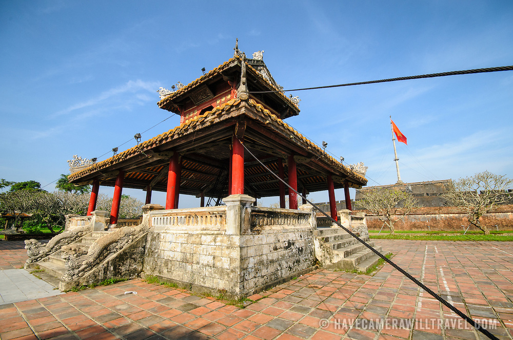 A wide-angle shot of a pagoda across the moat outside the Imperial City in Hue, Vietnam. A self-enclosed and fortified palace, the complex includes the Purple Forbidden City, which was the inner sanctum of the imperial household, as well as temples, courtyards, gardens, and other buildings. Much of the Imperial City was damaged or destroyed during the Vietnam War. It is now designated as a UNESCO World Heritage site.