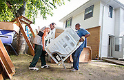 MILWAUKEE, WI — AUGUST 8, 2014: Johnny Zabala and Rashad Yarbrough with Eagle Moving and Storage Company removes a clothes dryer from 4350 88th Avenue on the North side of Milwaukee during a tenant eviction.