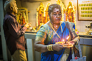 22 DECEMBER 2012 - SINGAPORE, SINGAPORE:  A woman carries a candle and oil lamp during prayers at the Sri Veeramakaliamman Temple, a Hindu temple located in Little India in Singapore. The Sri Veeramakaliamman Temple is dedicated to the Hindu goddess Kali, fierce embodiment of Shakti and the god Shiva's wife, Parvati. Kali has always been popular in Bengal, the birthplace of the labourers who built this temple in 1881. Images of Kali within the temple show her wearing a garland of skulls and ripping out the insides of her victims, and Kali sharing more peaceful family moments with her sons Ganesha and Murugan. The building is constructed in the style of South Indian Tamil temples common in Tamil Nadu as opposed to the style of Northeastern Indian Kali temples in Bengal.      PHOTO BY JACK KURTZ