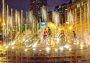Two Boys, Brothers or Dad and Son standing in city fountain and water jets and steam shoot around them.  Night in Boston urban park, Rose Kennedy Greenway.  Children play in water families look on.  Gold, Yellow and Green light with window lit buildings in Background..Lifestylle