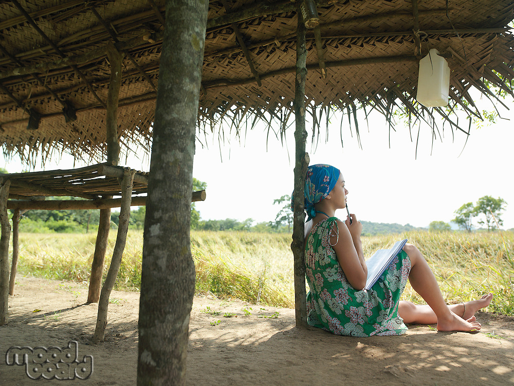 Young woman wearing dress sitting in shade of hut