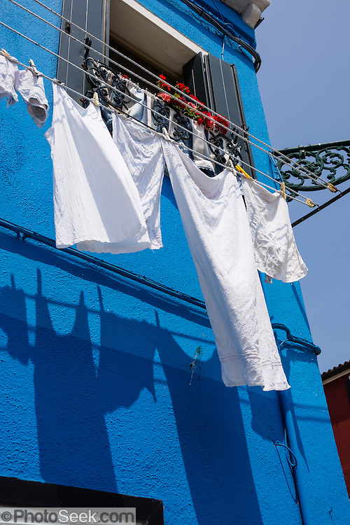 "White laundry drying outdoors casts shadows onto blue house. Burano, known for knitted lacework, fishing, and colorfully painted houses, is a small archipelago of four islands linked by bridges in the Venetian Lagoon, in the Veneto region of Italy, Europe. Burano's traditional house colors are strictly regulated by government. The Romans may have been first to settle Burano. Romantic Venice (Venezia), ""City of Canals,"" stretches across 100+ small islands in the marshy Venetian Lagoon along the Adriatic Sea in northeast Italy, between the mouths of the Po and Piave Rivers. Venice and the Venetian Lagoon are honored on UNESCO's World Heritage List."