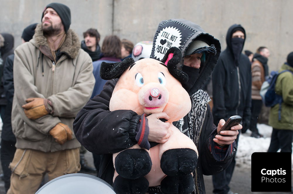 """An encircled protester holds a plush pig toy after being """"Kettled"""" by riot police. March 15, 2015."""