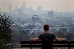 LNP HIGHLIGHTS OF THE WEEK 04/04/14 © licensed to London News Pictures. London, UK 01/04/2014. A man watching foggy London in Hampstead Heath on Tuesday, 1 April 2014 as The Met Office has forecast one of the year's worst smogs in London this week, following a combination of strong winds and powerful dust storms. Photo credit: Tolga Akmen/LNP