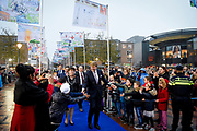 Koning Willem-Alexander wandelt op een blauwe loper door een zee van zelfgemaakte vlaggen door kinderen van 19 basisscholen voor aanvang van een feestelijke bijeenkomst in het stadhuis ter gelegenheid van het 50-jarig bestaan van de gemeente<br /> <br /> King Willem-Alexander walks on a blue runner through a sea of ​​homemade flags by children of 19 primary schools before commencement of a festive meeting in the town hall on the occasion of the 50th anniversary of the town