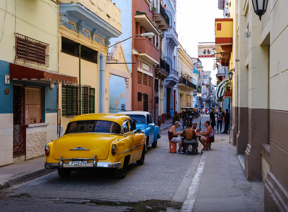 HAVANA, CUBA - CIRCA MAY 2017:  Old classic cars in the streets of Havana with people playing Domino.