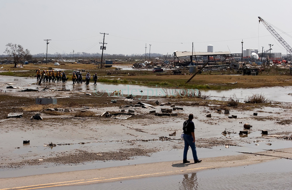 26 Sept, 2005. Cameron, Louisiana.  Hurricane Rita aftermath. <br /> Members of the Las Vegas, Nevada Task Force 1, a FEMA search and rescue team scour the destroyed remains of houses and business in Cameron, Louisiana for any signs of life two days after the storm ravaged the small town. A FEMA official steps out to greet rescuers as they arrive.<br /> Photo; ©Charlie Varley/varleypix.com