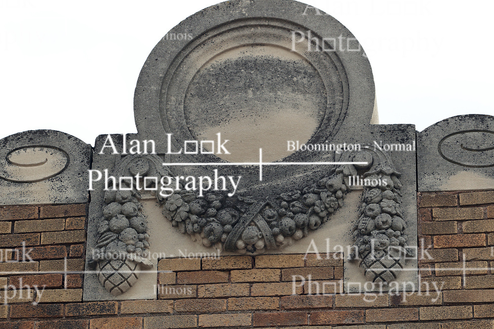 Ornate concrete building detail shows a circle with a fruit and berry wreath below and small scrolling to the sides