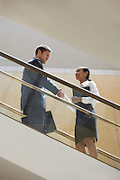 Businessman and Businesswoman on Escalator