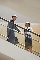 Businessman and Businesswoman on Escalator