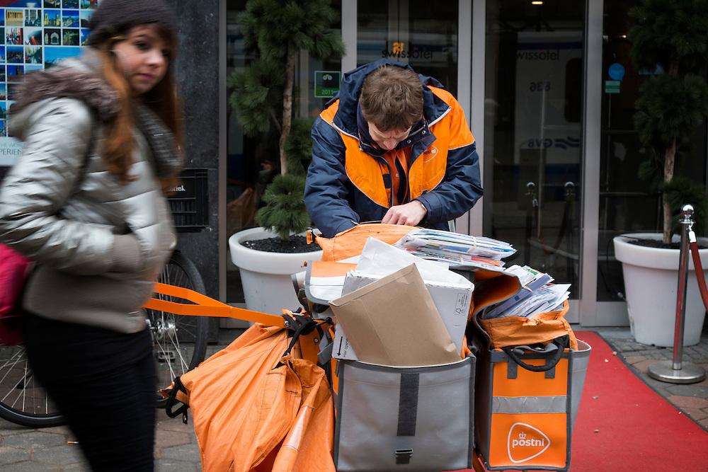Nederland, Amsterdam, 28 febr 2013.Postbezorger van tnt post op het damrak kijkt in zijn karretje welke poststukken hij moet bezorgen..Foto(c): Michiel Wijnbergh
