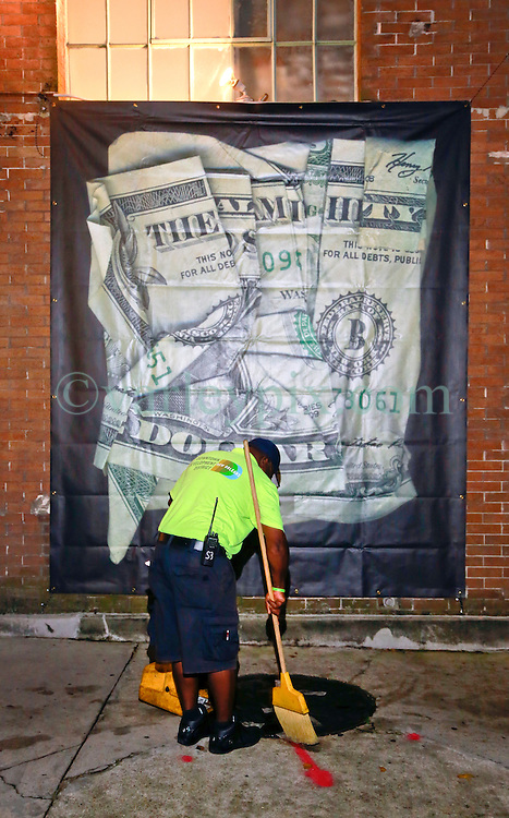 05 October 2013. New Orleans, Louisiana.<br /> Dan Tague and his Almighty Dollar bills at Jonathan Ferrara Gallery. A street cleaner sweeps away original Dan Tague dollar bills from the pavement outside the gallery.<br /> Photo; Charlie Varley