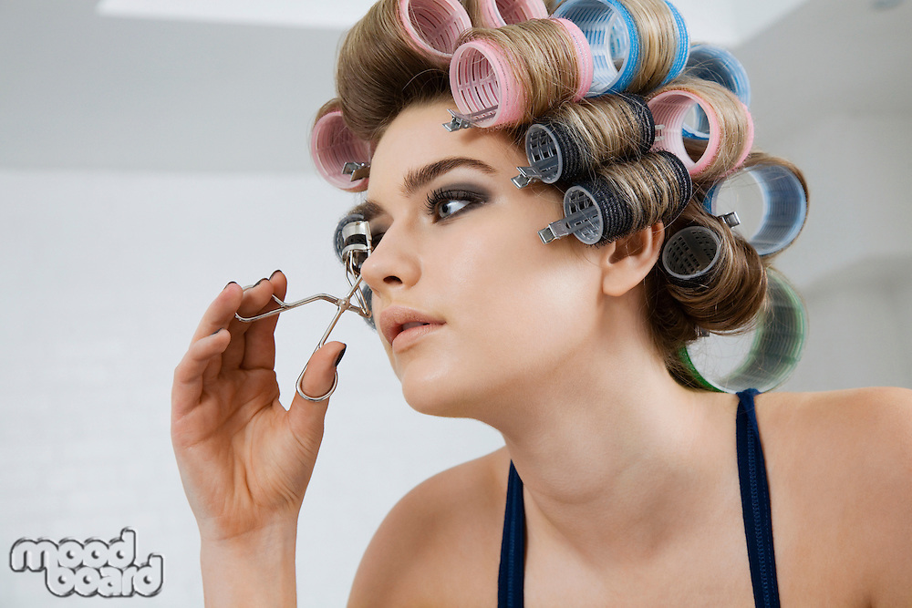 Model in Hair Curlers Using Eyelash Curler
