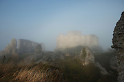 LES ANDELEYS, FRANCE - OCTOBER 10: Remains of the outer wall with the embossed ramparts of the Chateau Gaillard in a fog in the background, on October 10, 2008 in Les Andelys, Normandy, France. The chateau was built by Richard the Lionheart in 1196, came under French control in 1204 following a siege in 1203. It was later destroyed by Henry IV in 1603 and classified as Monuments Historiques in 1852. (Photo by Manuel Cohen/)