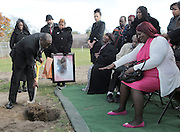 Clinton buries Batey's urn during a burial service for Batey at Oak Hill Cemetery in Gary.