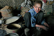Arkansas Democrat-Gazette/BENJAMIN KRAIN 10-27-03<br /> A young boy works unpaid in a blacksmith shop in Kabul. The shop keeper claims the boy is gaining valuable experience as an apprentice. Thousands of children toil in shops and factories throughout Afghanistan for little or no money.erience to one day open his own shop.